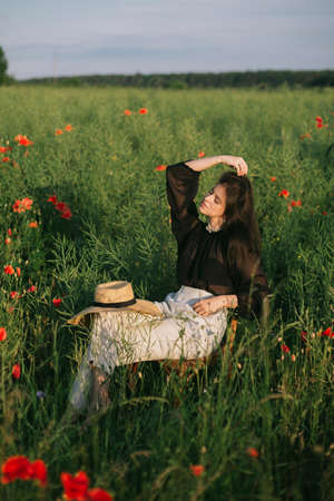 Slow living. Stylish elegant girl sitting on rustic chair in summer meadow with flowers. Fashionable young woman relaxing in field in evening light. Creative beautiful image.