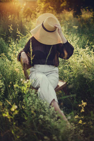 Stylish elegant girl in straw hat sitting on rustic chair in sunset light in summer meadow. Fashionable woman relaxing in summer countryside. Creative image. 免版税图像