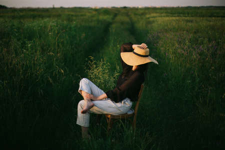 Stylish elegant girl in straw hat sitting on rustic chair in summer green meadow in evening sunlight. Fashionable young woman relaxing in field, tranquil moment.  Vacation in countryside 免版税图像