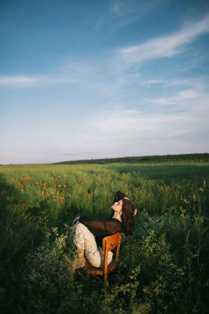 Summer countryside. Stylish elegant girl sitting on rustic chair in summer meadow with flowers. Fashionable young woman relaxing in field in evening light. Creative beautiful image. 免版税图像