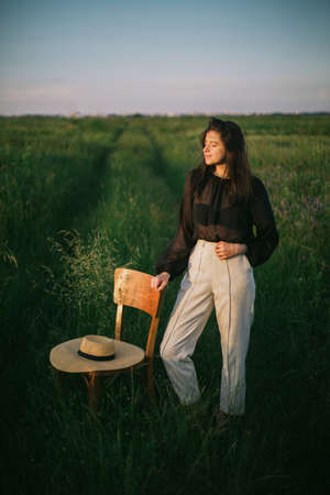 Stylish elegant girl standing  at rustic chair with straw hat in summer green field in evening sunlight. Fashionable young woman relaxing in summer countryside. Creative image