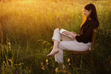 Young business woman working online. Freelance and remote work outdoors. Creative image. Fashionable elegant girl with laptop sitting on rustic chair in sunny summer field at sunset. 免版税图像