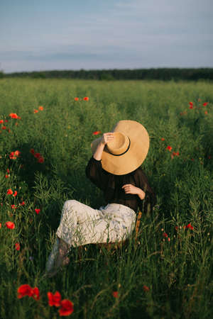 Fashionable young woman relaxing in field in evening light. Creative beautiful image. Slow living. Stylish elegant girl in hat sitting on rustic chair in summer meadow with flowers.