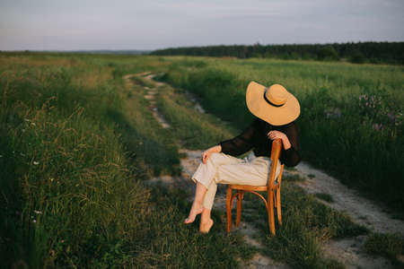 Slow living. Stylish elegant girl in straw hat sitting on rustic chair in summer meadow in evening. Fashionable young woman relaxing in field, tranquil moment. Creative image 免版税图像