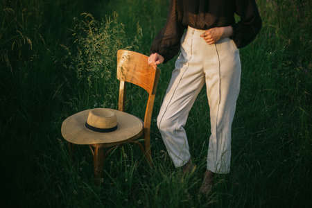 Stylish elegant girl standing at rustic chair with straw hat in summer green field in evening sunlight, cropped view. Relaxing in summer countryside. Creative image
