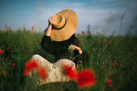 Slow living. Stylish elegant girl holding hat and sitting on rustic chair in summer meadow with flowers. Fashionable young woman relaxing in field in evening light. Creative image. 免版税图像