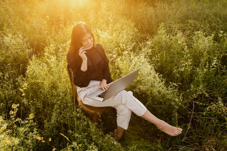 Fashionable elegant girl working on laptop and sitting on rustic chair in warm sunshine in summer meadow at sunset. Freelance. Creative image. Young business woman working online outdoors
