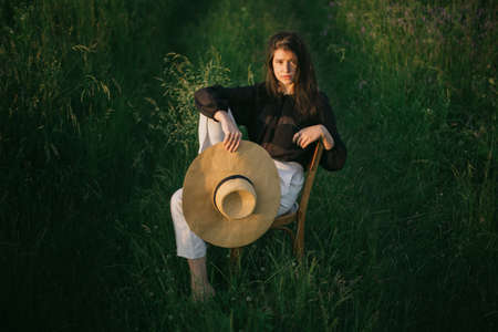 Stylish elegant girl holding straw hat and sitting on rustic chair in summer green field in evening sunlight. Fashionable young woman posing in summer countryside. Creative image