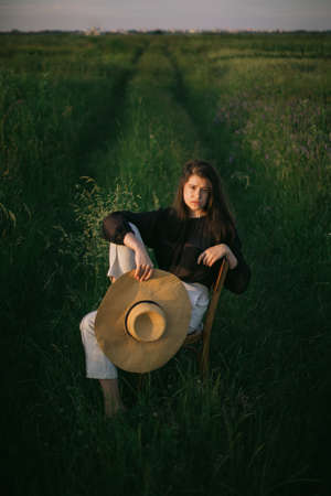 Fashionable young woman posing in summer countryside. Creative image. Stylish elegant girl holding straw hat and sitting on rustic chair in summer green field in evening sunlight.