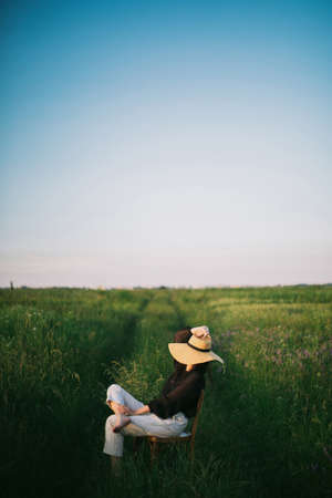 Stylish elegant girl in straw hat sitting on rustic chair in summer green meadow in evening sunlight. Fashionable young woman relaxing in field, tranquil moment.