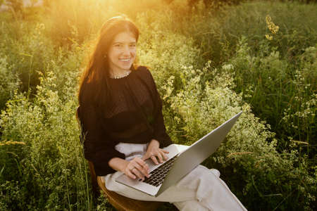 Fashionable elegant girl working on laptop and sitting on rustic chair in warm sunshine in summer meadow at sunset. Young business woman working online outdoors. New office concept