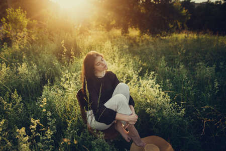 Fashionable woman relaxing in summer countryside. Stylish elegant girl sitting on rustic chair in sunset light in summer meadow.Atmospheric tranquil moment. Creative image.