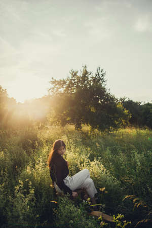 Slow living. Fashionable woman relaxing in summer countryside. Stylish elegant girl sitting on rustic chair in sunset light in summer meadow. Tranquil moment. Creative image. 免版税图像