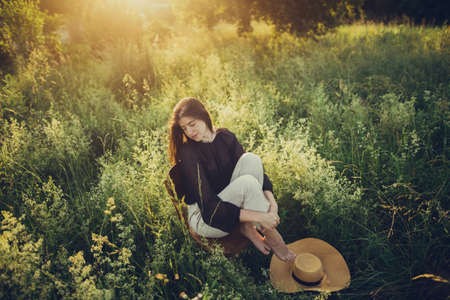 Stylish elegant girl sitting on rustic chair in sunset light in summer meadow. Fashionable woman relaxing in summer countryside. Creative image. Atmospheric tranquil moment