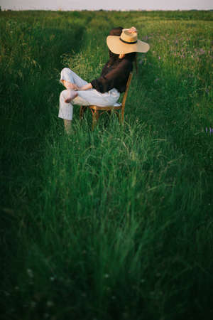 Slow living. Stylish elegant girl in straw hat sitting on rustic chair in summer green meadow in evening sunlight. Fashionable young woman relaxing in field, tranquil moment. Creative image