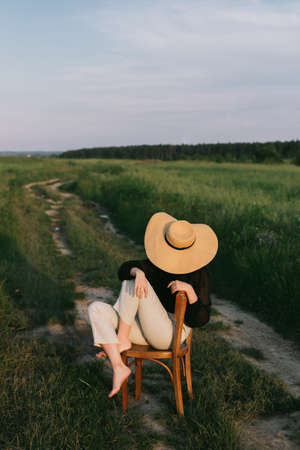 Stylish elegant girl in straw hat sitting on rustic chair in summer meadow in evening. Fashionable young woman relaxing in field, tranquil moment. Creative image. Summer countryside