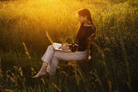 Fashionable elegant girl with laptop sitting on rustic chair in sunny summer field at sunset. Young business woman working online. Freelance and remote work outdoors. Creative image