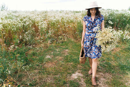 Stylish young woman in blue vintage dress and hat gathering white wildflowers in straw basket in meadow. Beautiful girl holding white daisies bouquet. Tranquil summer in countryside