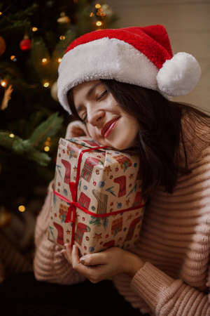 Stylish young woman holding christmas gift box and dreaming under christmas tree with lights in modern room. Happy girl in santa hat receiving christmas present. Happy holidays