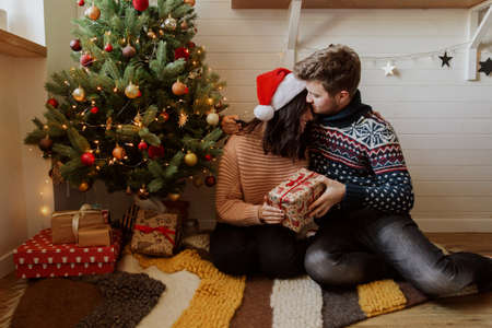 Stylish happy couple exchanging christmas gifts under christmas tree with lights. Young family hugging and holding present, happy moment in festive modern room. Happy holidays