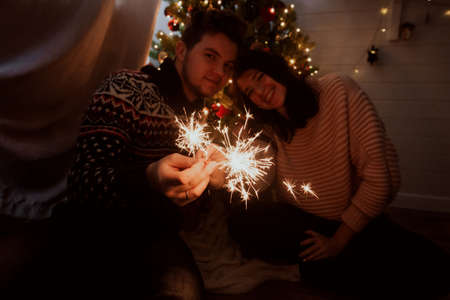 Young family with burning sparklers celebrating together in festive dark room. Happy New Year. Happy couple holding fireworks under christmas tree with lights.