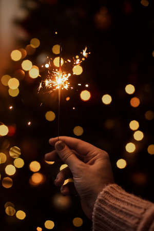 Burning sparkler in hand on background of golden bokeh lights in festive dark room. Happy New Year. Hand holding firework at christmas tree with golden illumination.