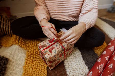 Woman wrapping red christmas gift box under christmas tree  in modern room, close up. Happy girl in sweater sitting and preparing christmas presents. Happy holidays Banco de Imagens