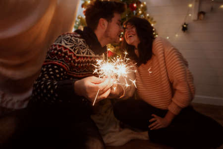 Happy couple holding fireworks under christmas tree with lights. Young family with burning sparklers celebrating together in festive dark room. Happy New Year