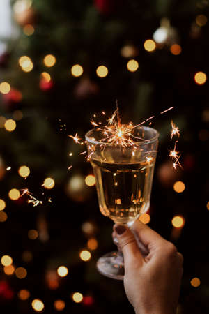 Happy New Year. Burning firework in champagne glass in hand on background of golden bokeh lights in festive room. Hand holding drink with sparkler at christmas tree. Creative aesthetic moment