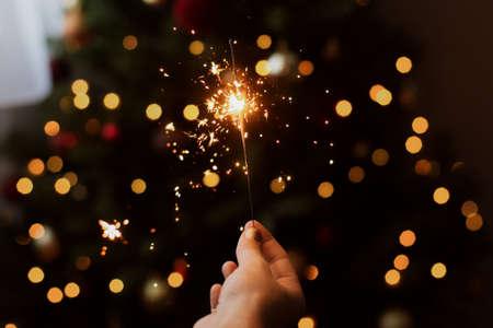 Happy New Year. Burning sparkler in hand on background of golden bokeh lights in festive dark room. Hand holding firework at christmas tree with golden illumination. Banco de Imagens