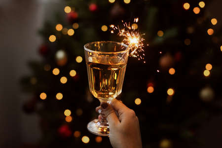 Burning firework in champagne glass in hand on background of golden bokeh lights in festive room. Happy New Year. Hand holding drink with sparkler at christmas tree. Creative aesthetic moment