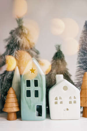 Merry Christmas. Christmas little houses and trees with golden lights bokeh on white background. Festive modern decor. Happy holidays. Miniature cozy village, ceramic houses, wooden trees.
