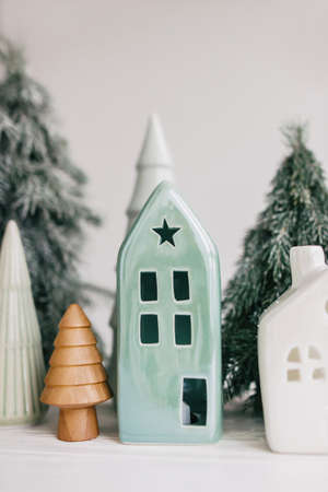 Christmas little houses and trees on white background. Holiday festive decor. Miniature village, ceramic houses, wooden christmas trees and handmade pine trees. Seasons greeting Banco de Imagens
