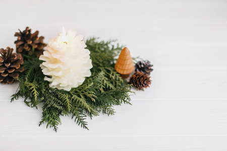 Christmas pine cone candle and tree in rustic christmas wreath on white wood. Small pine tree and modern wreath from white cedar and pine cones. Festive modern decor. Copy space