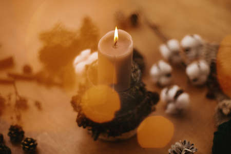 Christmas rustic candle in festive lights bokeh on wooden table with pine cones, cotton,anise and branches. Cozy moody winter evening. Rustic christmas candle decor on table. Banco de Imagens