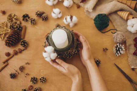 Making rustic christmas candle holder decor. Flat lay. Hands holding rustic candle on wooden table with cotton, branches, pine cones, anise and scissors. Holiday workshop