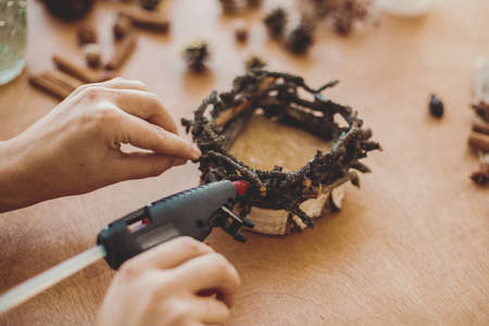 Process of making rustic christmas candle. Hands holding glue gun and making rustic festive decoration from branches, pine cones and cotton on wooden table. Holiday workshop
