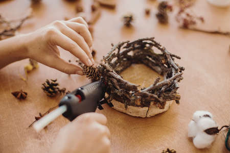 Hands holding glue gun and making rustic festive decoration from  pine cones, branches, and cotton on wooden table. Holiday workshop. Making rustic christmas candle holder. Banco de Imagens