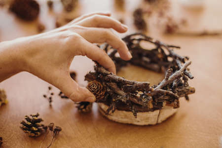 Florist making rustic christmas candle holder. Hands holding pine cones and branches and making rustic festive decoration on wooden table. Holiday workshop