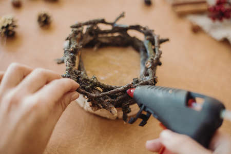 Making rustic christmas candle holder. Hands holding glue gun and making rustic festive decoration from branches, pine cones and cotton on wooden table. Holiday workshop