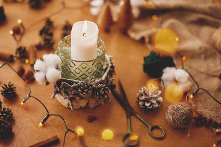 Christmas candle in rustic holder made of branches, cotton, anise and pine cones on wooden table with festive lights. Holiday workshop. Making rustic christmas candle decor. Banco de Imagens
