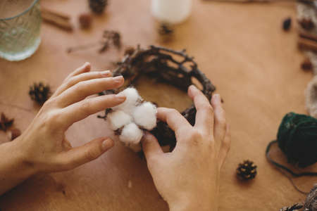 Florist making rustic christmas candle holder. Hands holding cotton and making rustic festive decoration on wooden table with branches and pine cones. Holiday workshop Banco de Imagens