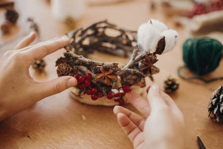 Florist making rustic christmas candle holder. Hands holding pine cones, branches, anise and making rustic festive decoration on wooden table. Holiday workshop
