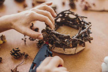 Hands holding glue gun and making rustic festive decoration from pine cones, branches, and cotton on wooden table. Holiday workshop. Making rustic christmas candle holder.