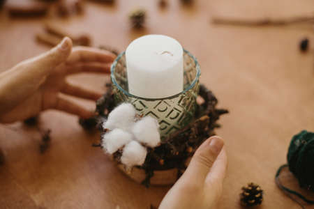 Florist making rustic christmas candle decor. Hands holding rustic candle holder on wooden table with cotton, branches, pine cones. Holiday workshop