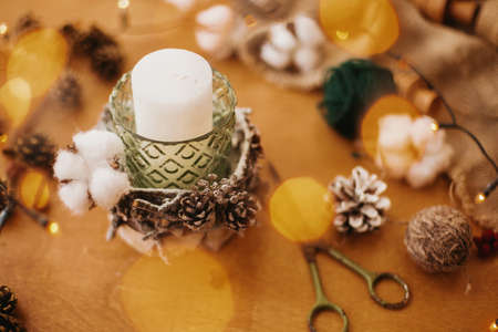 Christmas candle in rustic holder made of branches, cotton, anise and pine cones on wooden table in festive lights bokeh. Making rustic christmas candle decor. Holiday workshop Banco de Imagens