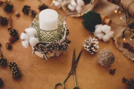 Making rustic christmas candle decor. Christmas candle in rustic holder made of branches, cotton, anise and pine cones on wooden table with festive lights. Holiday workshop Banco de Imagens