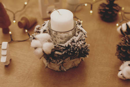 Christmas candle in rustic holder made of branches, cotton, anise and pine cones on wooden table with festive lights. Making rustic christmas candle decor. Holiday workshop Banco de Imagens