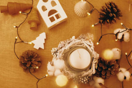 Christmas rustic candle, pine cones, wooden tree, toy house and  festive lights on wood. Rustic christmas candle decor on table. Winter holiday Banco de Imagens