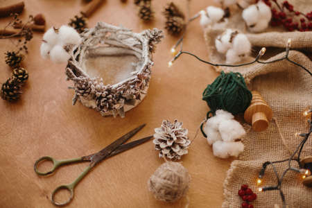 Making rustic christmas candle decor. Christmas candle  holder made of branches, cotton, anise and pine cones on wooden table with festive lights. Holiday workshop.